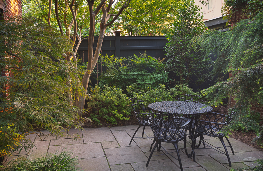 A secluded dining area nestled among azaleas and a lovely Japanese maple.